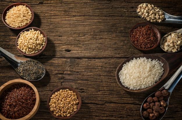 Vari tipi di cereali (grano, riso, riso integrale, grano saraceno, orzo, sesamo nero, miglio, semi di loto, lacrime di giobbe) vari cereali crudi non cotti su fondo in legno.