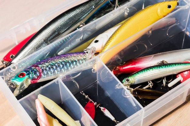 Vari tipi di esche da pesca nel contenitore bianco