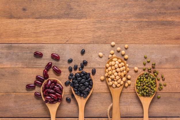 Vari tipi di fagioli naturali, rosso, nero, verde e soia in cucchiai sulla tavola di legno, vista superiore