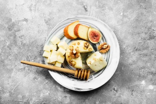 Vari tipi di formaggi, fichi, noci, miele