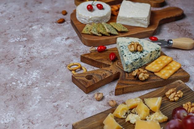Vari tipi di formaggi su superficie marrone chiaro
