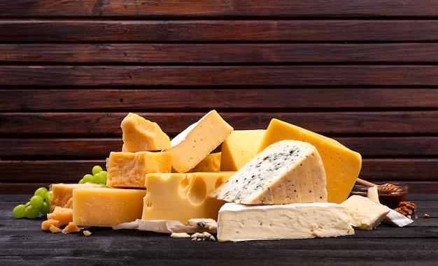 Vari tipi di formaggi sul tavolo in legno nero.