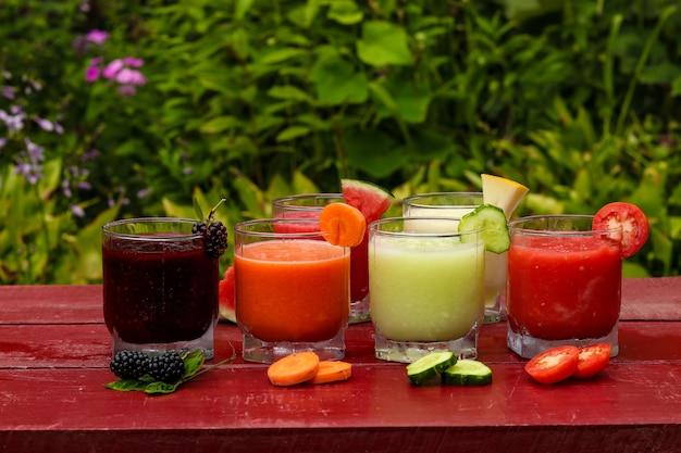 Vari tipi di frullati di frutta e verdura fatti di anguria, cetrioli, pomodori, meloni, carote e more