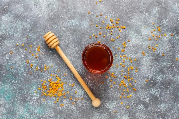 Vari tipi di miele in barattoli di vetro, favo e polline.