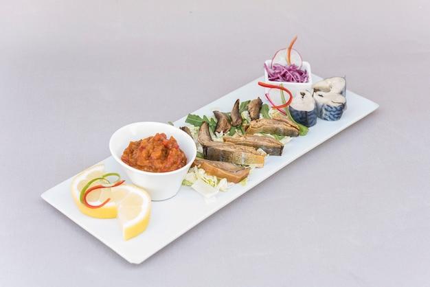 Vari tipi di pesce, affumicato e marinato, con insalata fresca, insalata di verdure, insalata di cipolle