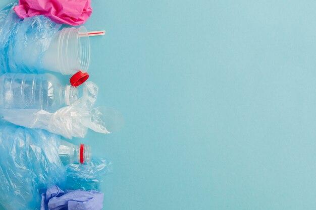 Vari tipi di rifiuti di plastica usa e getta su sfondo blu