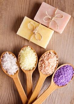 Vari tipi di sale marino termale e sapone in primo piano di cucchiai di legno
