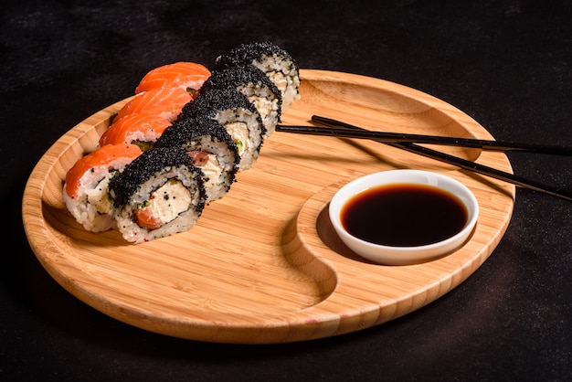 Vari tipi di sushi sono serviti al buio. rotolo con salmone, avocado, cetriolo. menu di sushi. cibo giapponese.