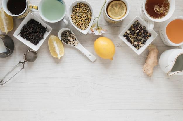 Vari tipi di tè con erbe e foglie secche sul tavolo di legno