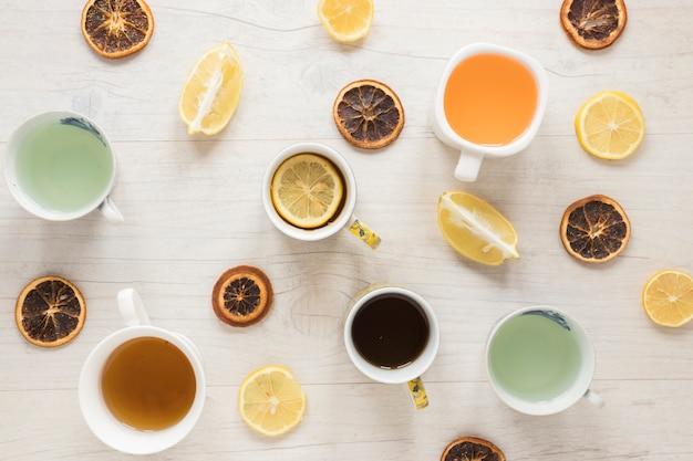 Vari tipi di tè in tazza di ceramica; fette di pompelmo secco con limone su fondo di legno