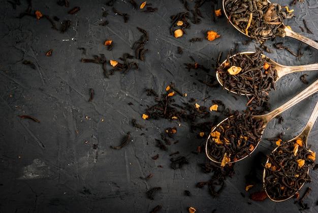Vari tipi di tè secco in cucchiai