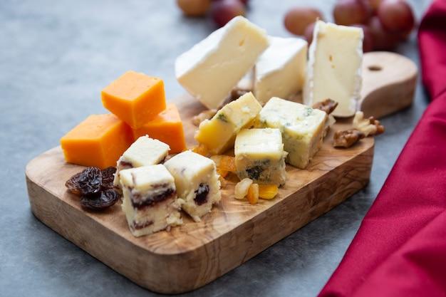 Vari tipi diversi di fette di formaggio, mix di formaggi sul tagliere di legno.