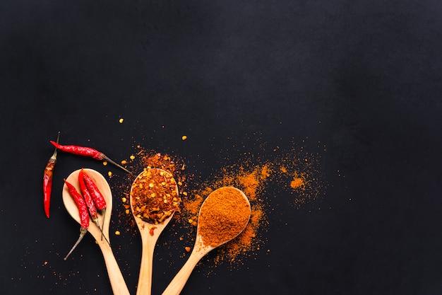 Varia spezia asciutta del peperoncino rosso in cucchiai di legno su fondo nero, vista superiore