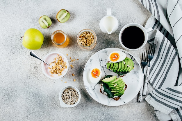 Variazione di colazione completa. toast di avocado, uova, yogurt con muesli, frutta, semi, caffè nero