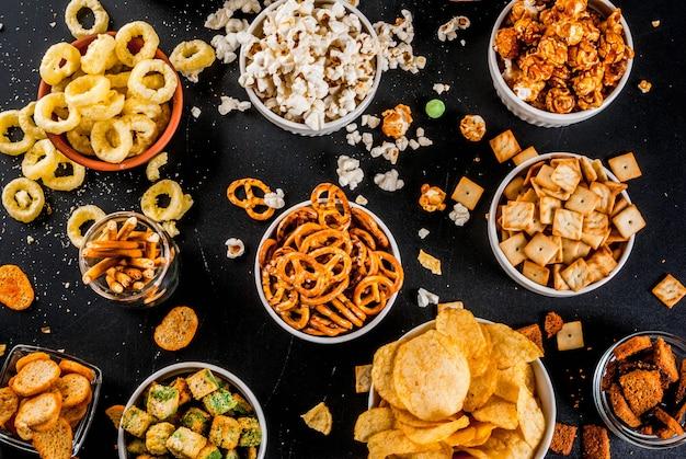 Variazione diversi snacker non salutari, popcorn dolci salati, tortillas, noci, cannucce, bretelle