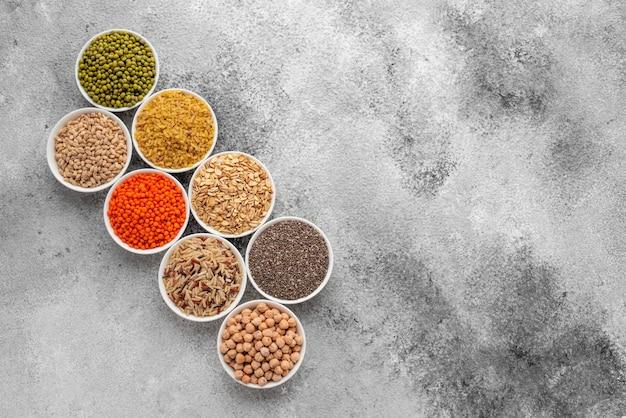 Variazioni di porridge e fagioli in piattini bianchi su uno sfondo grigio cemento