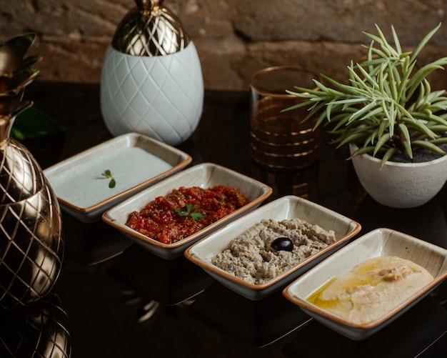 Variazioni di salse per barbecue, tra cui yogurt pomodoro olive e salse all'olio