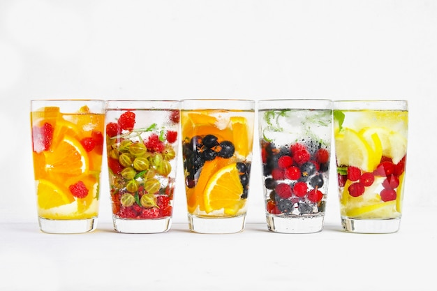 Varie acque disintossicanti in bicchieri, gusti diversi, bacche, frutti.