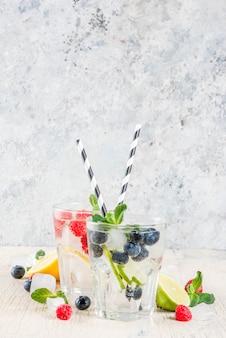 Varie bacche di limonata o mojito cocktail di ghiaccio fresco limone lime lampone mirtillo infuso acqua estate disintossicazione sana bevande sfondo chiaro
