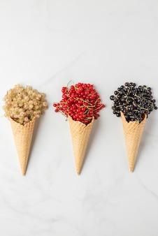 Varie bacche di ribes in coni gelato waffle su marmo bianco. ribes rosso, bianco e nero. vista dall'alto