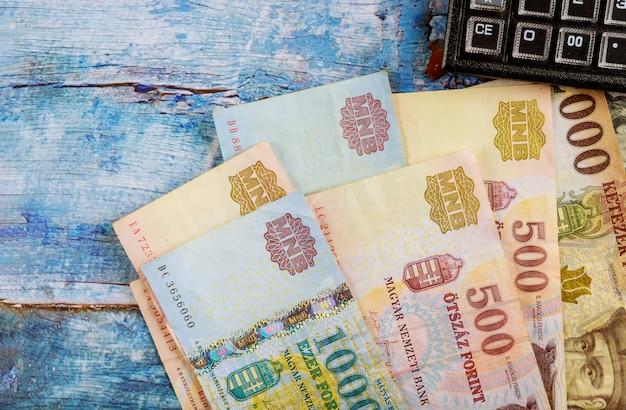 Varie banconote ungheresi dei fiorini con il calcolatore sulla tavola in ufficio