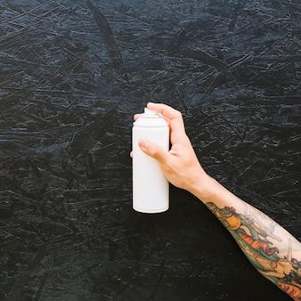 Varie bottiglie bianche in fila su superficie nera ruvida