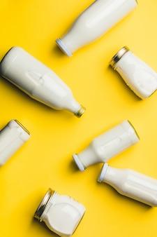 Varie bottiglie di latte su sfondo giallo