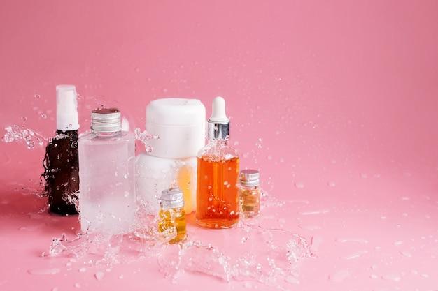 Varie bottiglie, vasetti e contenitori con cosmetici sul rosa con spruzzi d'acqua. concetto di prodotti idratanti naturali per la cura della pelle