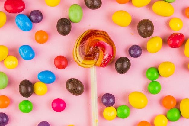 Varie caramelle dolci che circondano lecca-lecca su fondo rosa