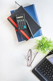 Varie cartolerie; occhiali da vista e pianta in vaso su tavolo