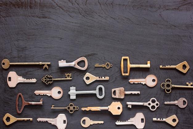 Varie chiavi di metallo su una superficie di legno nera