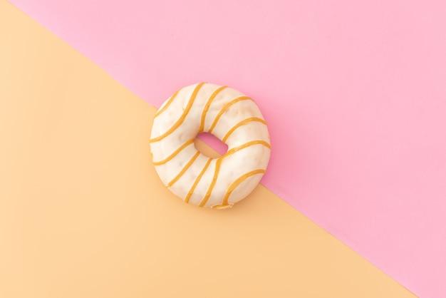 Varie ciambelle decorate in movimento che cade su sfondo rosa. ciambelle dolci e colorate che cadono o volano in movimento.