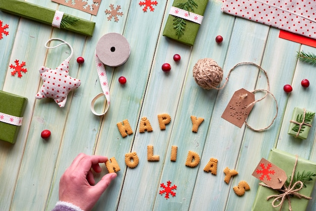 Varie decorazioni eco-compatibili per le vacanze invernali di natale o capodanno, confezioni di carta artigianale e vari regali a zero rifiuti. piatto disteso su legno verde, mano e scritta