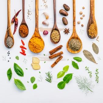 Varie erbe e spezie in cucchiai di legno su fondo in legno.