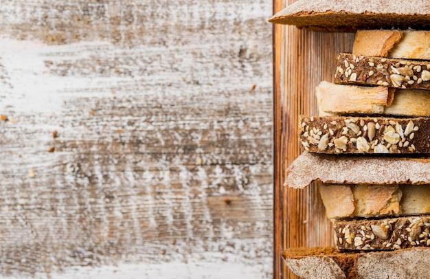 Varie fette di pane appena sfornato fresco in vassoio di legno