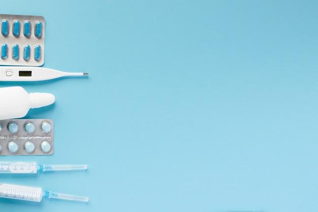 Varie medicine, un termometro, spruzzi da un naso chiuso e un dolore alla gola su sfondo blu
