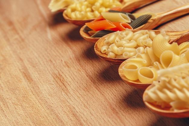 Varie paste su cucchiai di legno