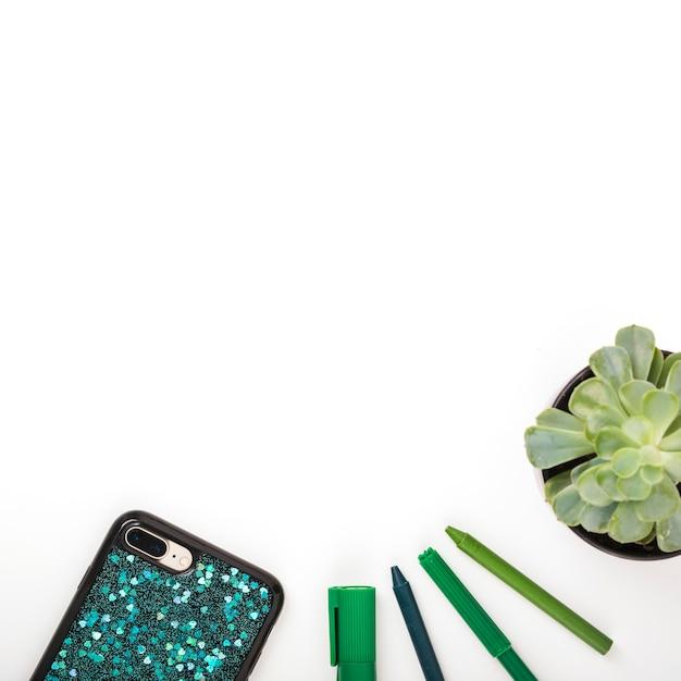 Varie penne con smartphone e pianta in vaso su sfondo bianco