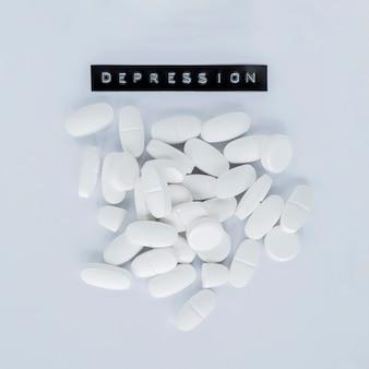 Varie pillole bianche con etichetta di depressione su sfondo grigio