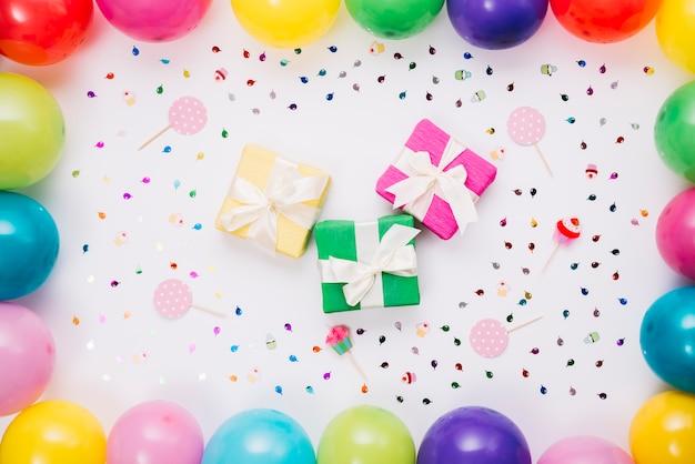 Varie scatole regalo decorate con confetti; puntelli e palloncini su sfondo bianco