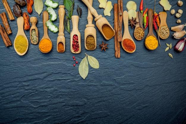 Varie spezie ed erbe aromatiche in cucchiai di legno sulla pietra nera.