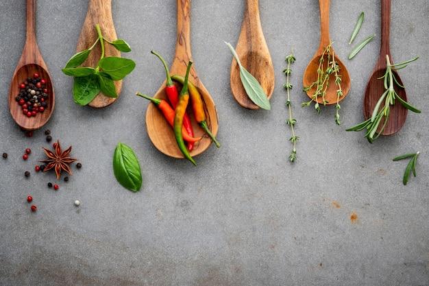 Varie spezie ed erbe aromatiche in cucchiai di legno.