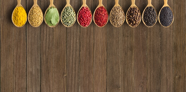 Varie spezie ed erbe in cucchiai di legno. condimenti vintage