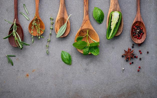 Varie spezie ed erbe in cucchiai di legno.