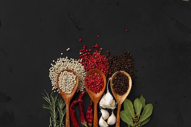 Varie spezie esotiche in cucchiai di legno su sfondo scuro