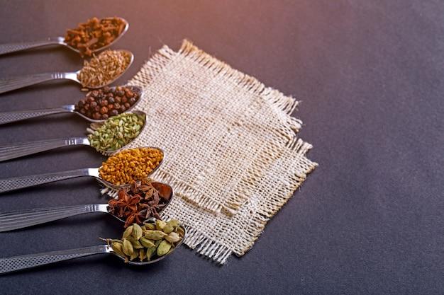 Varie spezie in cucchiai su fondo bianco