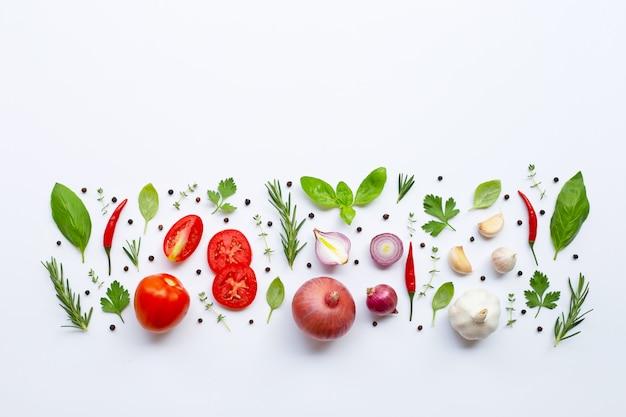 Varie verdure fresche ed erbe su sfondo bianco. concetto di mangiare sano