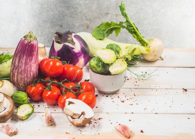 Varie verdure organiche fresche su superficie di legno
