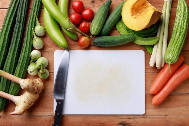Varie verdure, spezie e ingredienti con un coltello