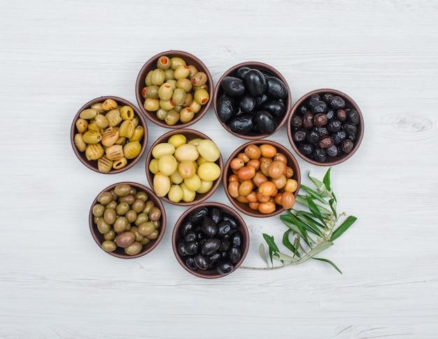 Varietà assortita di olive in ciotole di argilla con la vista superiore delle foglie di olivo su legno bianco